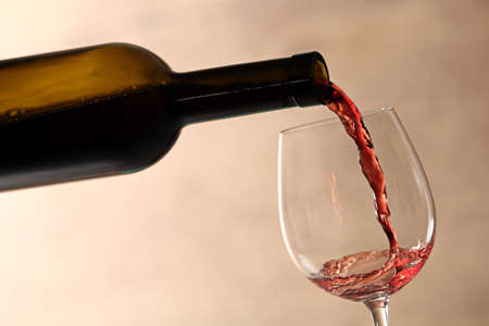 Pouring red wine into glass from bottle against blurred beige background, closeup