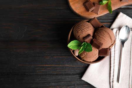 Flache Zusammensetzung mit Schüssel Schokoladeneis und Minze auf Holztisch, Platz für Text, Standard-Bild