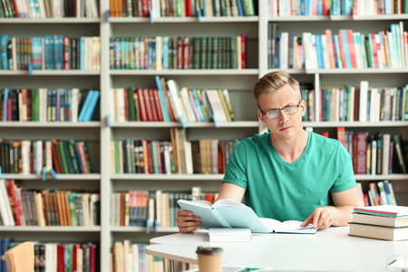 Pensive young man with books at table in library. Space for text