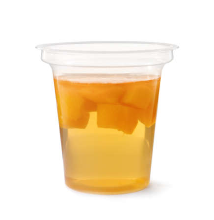 Tasty jelly dessert with slices of fruit in plastic cup on white background