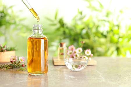 Goteo de aceite esencial de árbol de té natural en una botella en la mesa, espacio para texto