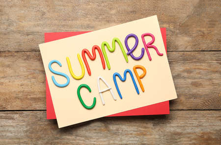 Text SUMMER CAMP made of modelling clay on wooden table, flat lay Stock fotó