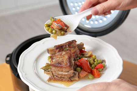 Woman putting meat and garnish prepared in multi cooker on plate, closeup