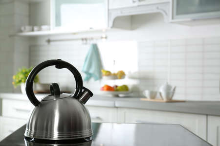 Modern kettle with whistle on stove in kitchen, space for text Stockfoto