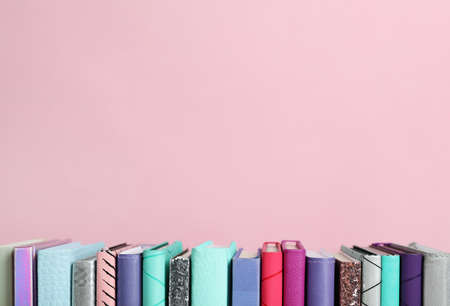 Composition with books on pink background. Space for text