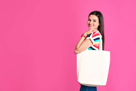 Beautiful young woman with stylish blank eco bag against color background, space for text