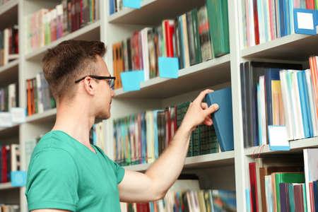 Junger Mann, der ein Buch aus dem Regal in der Bibliothek nimmt