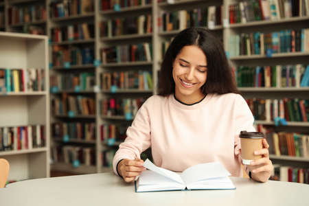 Young woman reading book at table in library. Space for text