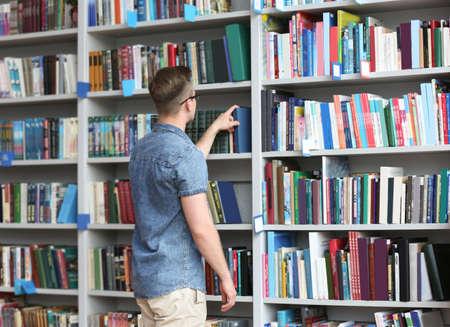 Joven tomando el libro de la estantería en la biblioteca. Espacio para texto Foto de archivo