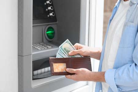 Man with money near cash machine outdoors, closeup Imagens