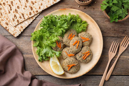 Flat lay composition with plate of traditional Passover (Pesach) gefilte fish on wooden background