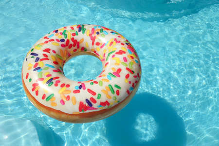 Bright inflatable doughnut ring floating in swimming pool on sunny day. Space for text