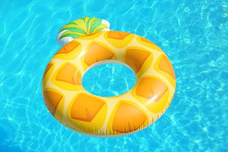 Anello gonfiabile luminoso dell'ananas che galleggia nella piscina il giorno soleggiato Archivio Fotografico