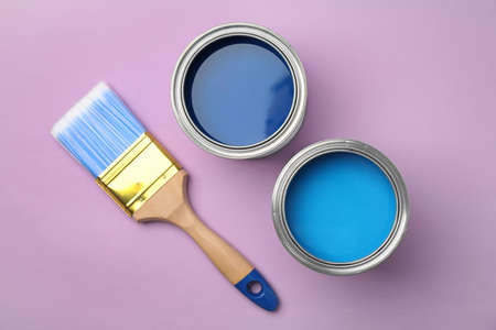 Flat lay composition with open cans of paint on color background