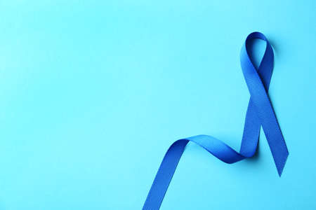 Blue ribbon on color background, top view with space for text. Colon cancer awareness concept
