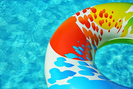 Colorful inflatable ring floating in swimming pool on sunny day. Space for text