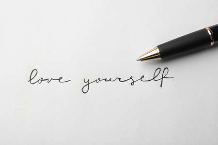 Written words LOVE YOURSELF and pen on white background, top view
