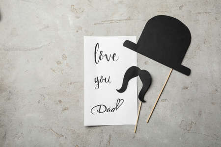 Note with words LOVE YOU DAD, paper hat and moustache on grey background, flat lay