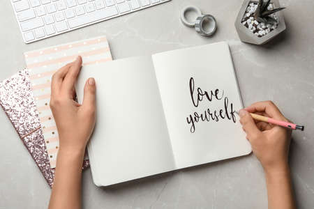 Mujer escribiendo AMATE A TI MISMO en diario sobre mesa gris, endecha plana