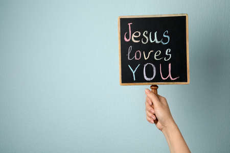 Woman holding chalkboard with words JESUS LOVES YOU on color background, closeup. Space for text