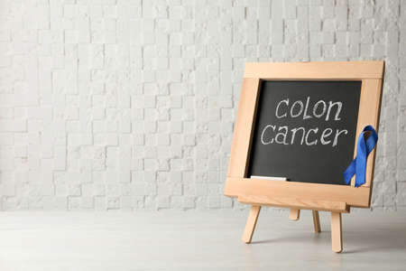 Chalkboard with blue ribbon and text Colon cancer awareness on table