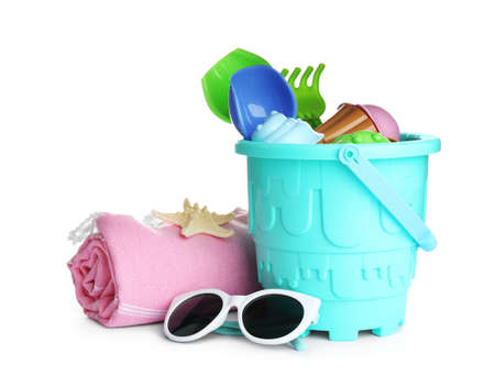 Set of plastic beach toys, sunglasses and blanket on white background