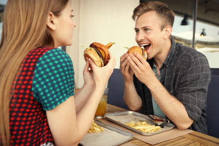 Young couple eating burgers in street cafe 写真素材