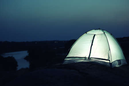 Small camping tent glowing in twilight outdoors. Space for text