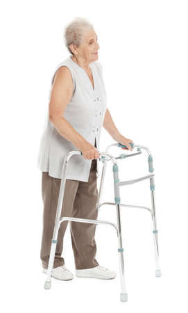 Full length portrait of elderly woman using walking frame isolated on white background