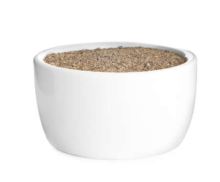 Bowl of ground black pepper isolated on white