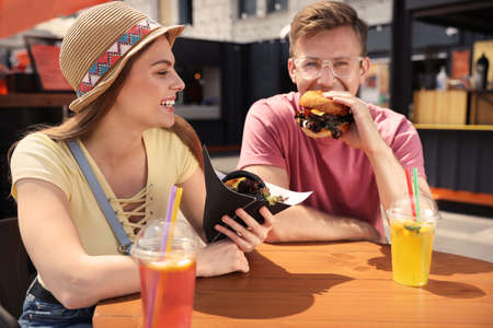 Young happy couple with burgers in street cafe 写真素材
