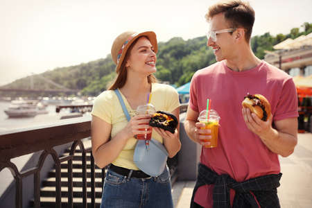 Young happy couple with burgers walking on city street Stock fotó