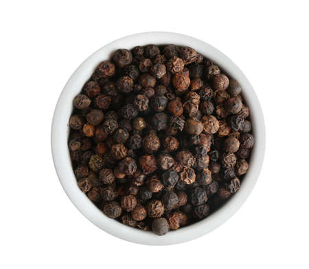 Bowl of black peppercorns isolated on white, top view