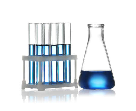 Test tubes in rack and conical flask with liquid samples on white background. Chemistry glassware