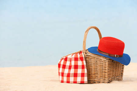 Wicker basket with blanket and hat on sand near sea, space for text. Beach picnic Stock Photo