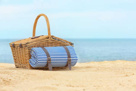 Wicker picnic basket with blanket on sand near sea, space for text