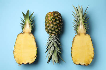 Fresh whole and cut pineapples on light blue background, top view