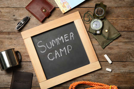 Chalkboard with text SUMMER CAMP and camping equipment on wooden background, flat lay