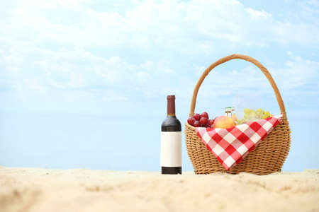 Wicker basket with food and wine on sand near sea, space for text. Beach picnic 写真素材
