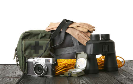 Set with different camping equipment on wooden table against white background