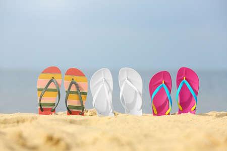Diferentes chanclas brillantes en arena. Accesorios de playa