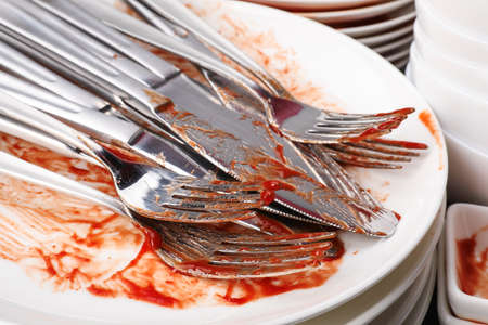 Stack of dirty dishes with cutlery, closeup