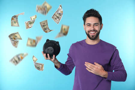 Happy young man with piggy bank and falling money on blue background