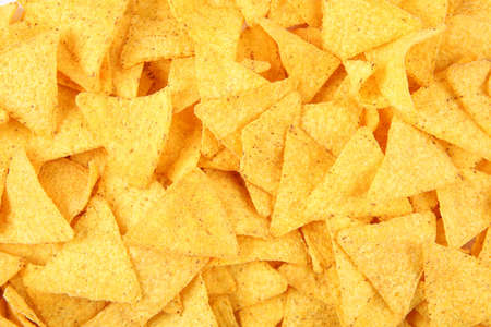 Tasty Mexican nachos chips as background, top view