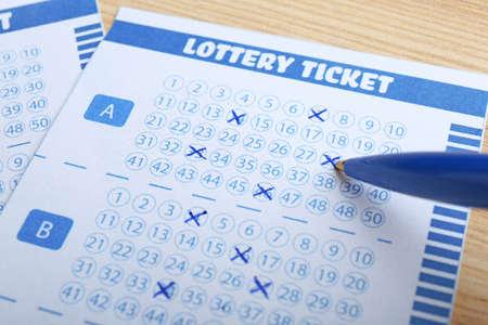 Llenar billetes de lotería con lápiz sobre mesa de madera, primer plano. Espacio para texto Foto de archivo