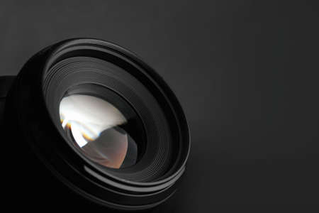 Modern camera lens on black background, closeup. Space for text