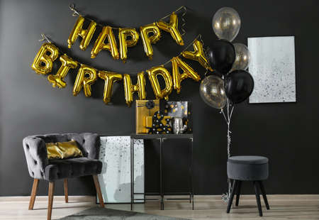 Room interior with gift boxes and phrase HAPPY BIRTHDAY made of golden balloon letters