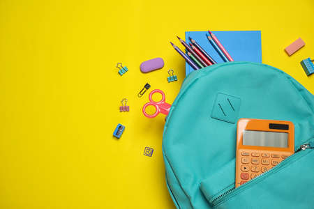 Stylish backpack with different school stationary on yellow background, top view. Space for text