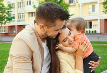 Happy family with adorable little baby outdoors