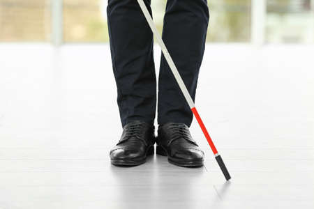 Blind person with long cane standing indoors, closeup
